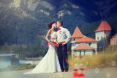 Bride and groom kissing on the background of mountains — Stock Photo