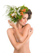 A beautiful naked girl with flowers on her head on a white backg — Stock Photo