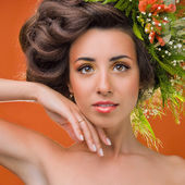 A beautiful girl with flowers on her head on an orange backgroun — Stock Photo