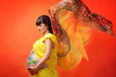 The pregnant girl with the drawn picture on a stomach in a yello — Stock Photo