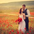 Bride and groom in poppy field — Stock Photo #26401219
