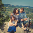 Family in striped shirts on background of mountains — Stok fotoğraf