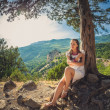 Beautiful woman near a tree high up on the mountains — Stock Photo