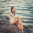 Beautiful young womsitting on stone on seashore — Stock Photo #27269053