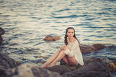 Beautiful young woman sitting on the stone on the seashore — Стоковое фото