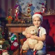 Young boy holding teddy bear near New Year tree — Stock Photo #35605809