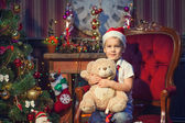 A young boy holding teddy bear near the New Year tree — Stock Photo