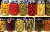 Various preserved fruits and vegetables in jars — Stock Photo