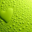 Water drops and heart shape on green background — Stock fotografie