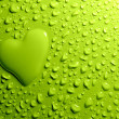 Water drops and heart shape on green background — Stock Photo