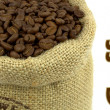 Roasted coffee beans in a flax bag and sample text — Stock Photo #13524923
