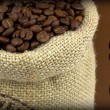 Coffee beans in a flax sack on brown background and sample text — Stock Photo #13524929