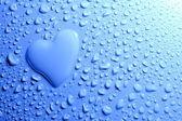 Gotas de agua y forma en el fondo azul del corazón — Foto de Stock