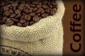 Kaffebönor i en lin säck på brun bakgrund och exempeltext — Stockfoto