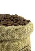 Pražená kávová zrna a plátěný pytel — Stock fotografie