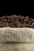 Chicchi di caffè in un sacchetto di lino su sfondo nero — Foto Stock