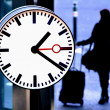 Stock Photo: Station clock and passenger waiting with suitcase.