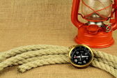 Old compass, oil lamp and rope on burlap — Stock Photo