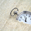 Pocket watch semi buried in the sand — Stock Photo