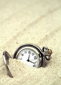 Antique pocket watch buried in sand — Stock Photo