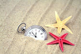 Zakhorloge en zeesterren op het zand — Stockfoto