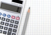 Calculator and lead pencil on squared paper — Stock Photo