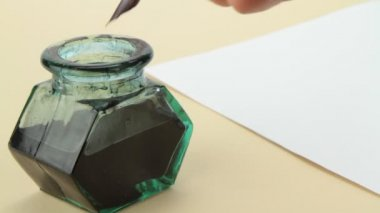 Ink bottle, quill pen and parchment . — Stock Video