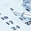 Ink pen and coin money on calendar — Stock Photo #12446840