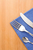 Silver fork and knife as utensils at napkin on wood — Stock Photo