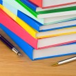 Pile of new book and pens on wood — Stockfoto