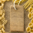 Raw pasta and price tag on sack hessian - Stock Photo