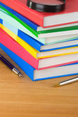 Pile of new book and pens on wood — Stock Photo