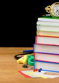 Pila de libros y útiles escolares aislados sobre fondo negro — Foto de Stock