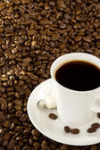 Cup of coffee at beans — Stock Photo