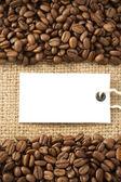 Kahve çekirdekleri ve kağıt fiyat etiketi çuval üzerinde — Stok fotoğraf