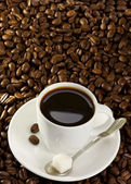 Full cup of coffee at beans — Stock Photo