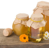 Honey in jar isolated on white background at old wood wood — Stock Photo