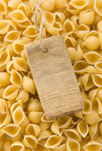 Raw pasta and price tag — Stock Photo