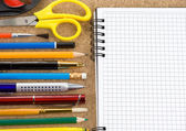 School accessories on checked notebook — Stock Photo