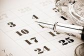 Ink pen and coin money on calendar — Stock Photo