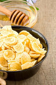 Bowl of corn flakes and honey on wood — Stock Photo
