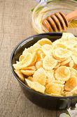 Bowl of corn flakes and honey — Stock Photo