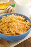 Bowl of corn flakes and milk on wood — Stock Photo