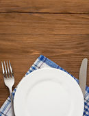 White plate, knife and fork on wood — Stockfoto