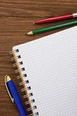 チェックのメモ帳と木の上のペン — ストック写真