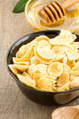 Bowl of corn flakes and honey — Stock Photo