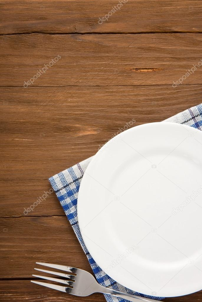 White plate and fork at napkin on wooden background — Stock Photo #16272667