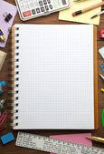 Schoolbenodigdheden en gecontroleerd notebook — Stockfoto