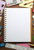School supplies and checked notebook — Stock Photo
