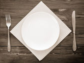 White plate, knife and fork on wood — Stock fotografie